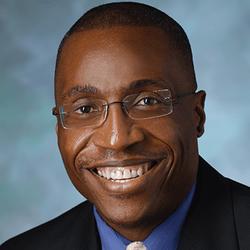 Headshot of KL2 Scholar Dr. Chukwuemeka Ihemelandu. He is smiling and wearing glasses.