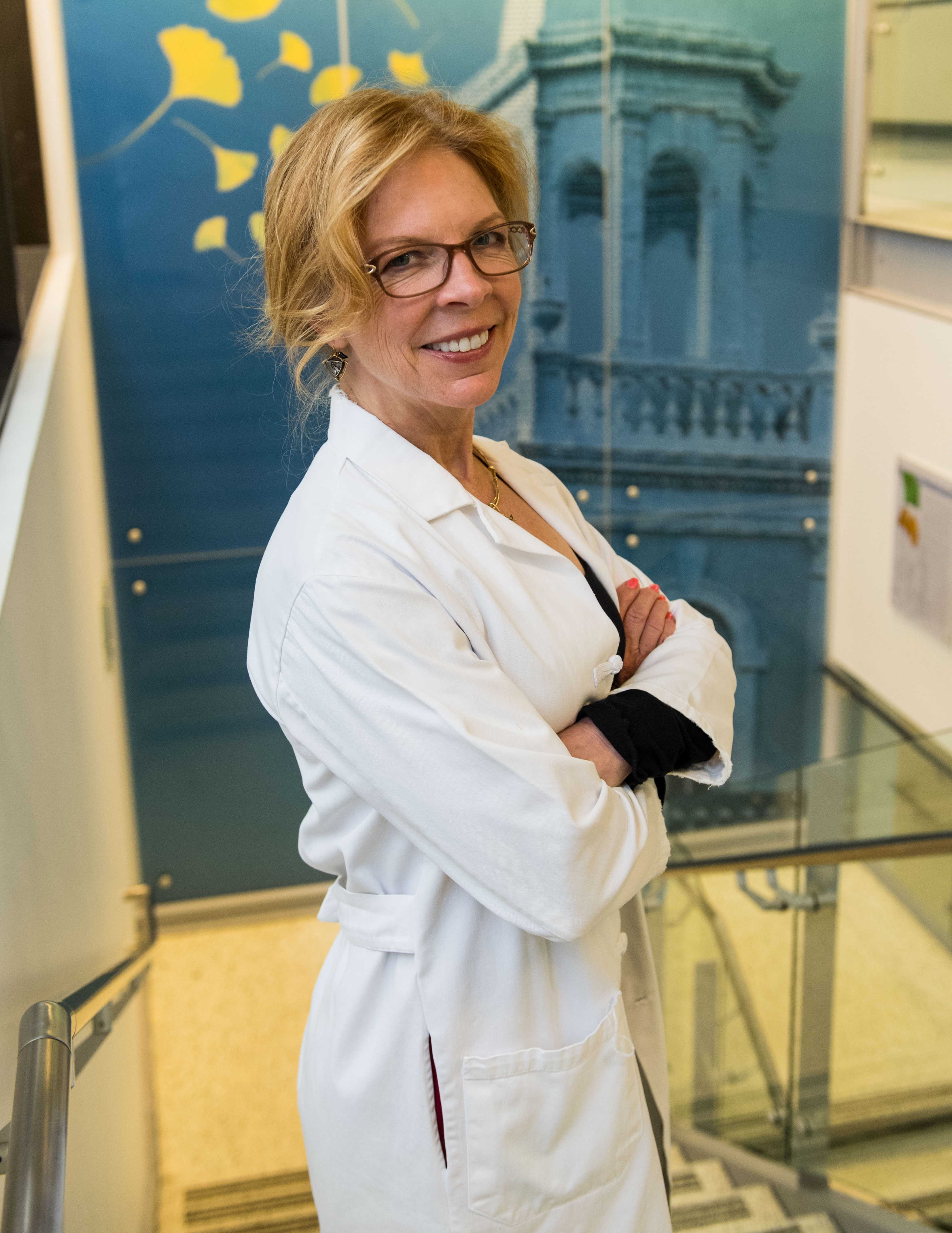 Photo of Kathryn Sandberg, PhD standing in a bright stairway wearing a white lab coat