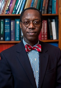 Headshot of Dr. Obisesan wearing a suit and striped bow-tie standing in a library
