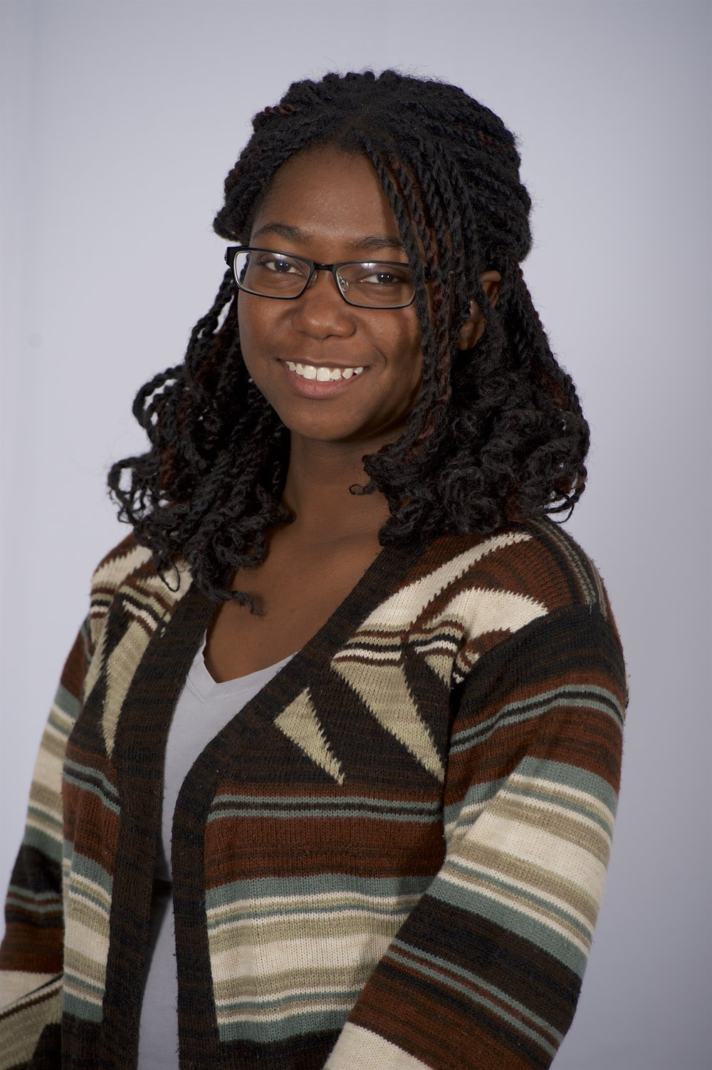 Photo of doctoral student Sikoya Ashburn wearing a striped sweater and glasses