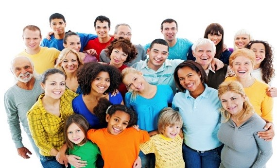 Large group of diverse people wearing bright clothing standing in a close circle