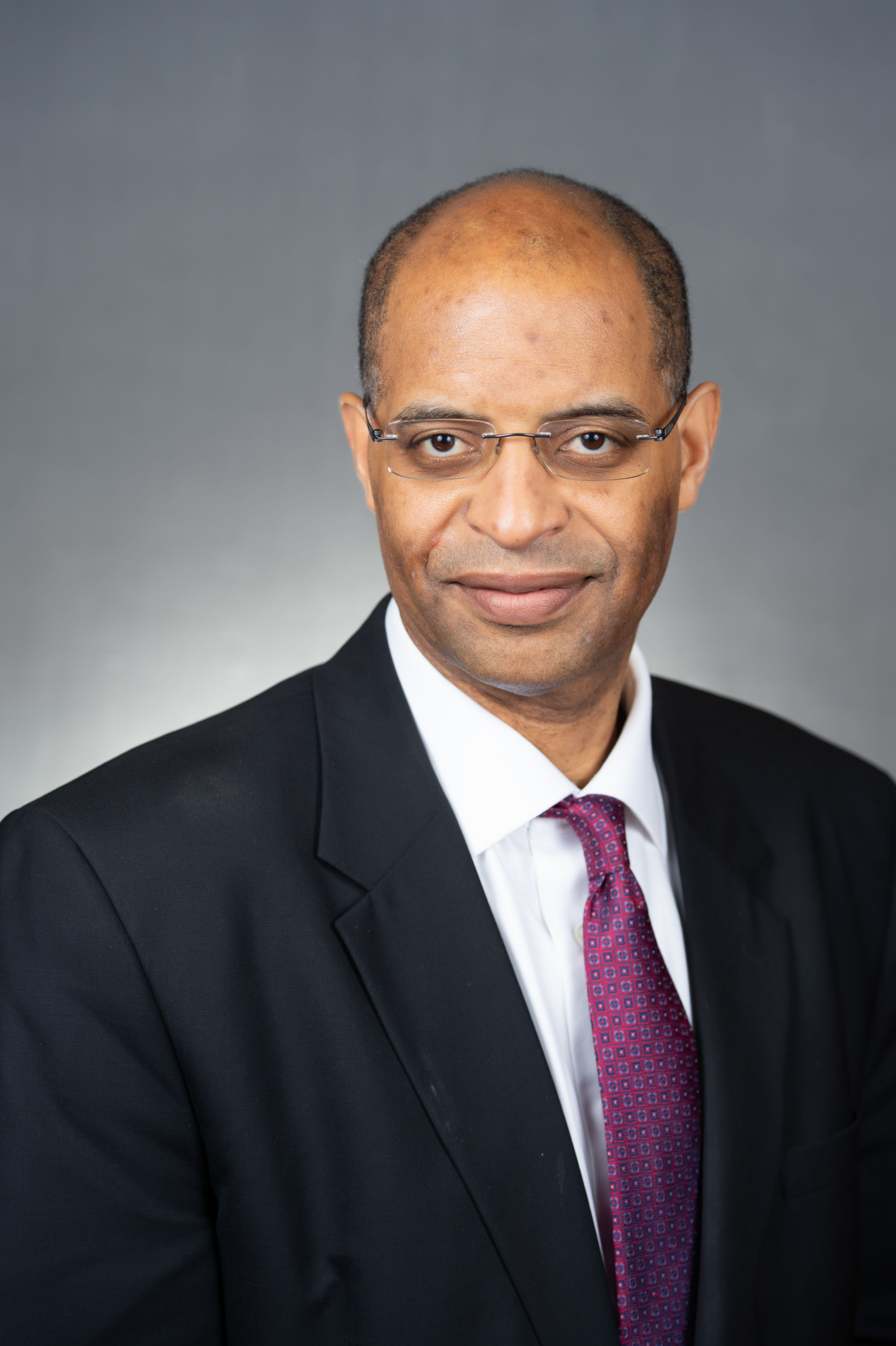 Headshot of Dr. John Carethers wearing a black suit and a blue tie