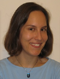 Headshot of Dr. Greenwald looking to the side, smiling, wearing a shiny necklace