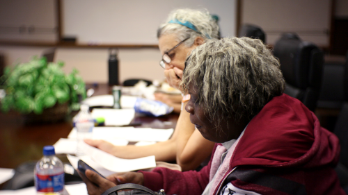 Two members of the GHUCCTS Participant Advisory Board reading a packet at a conference table