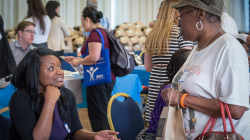 Two women talking to each other across an information table at a resource fair